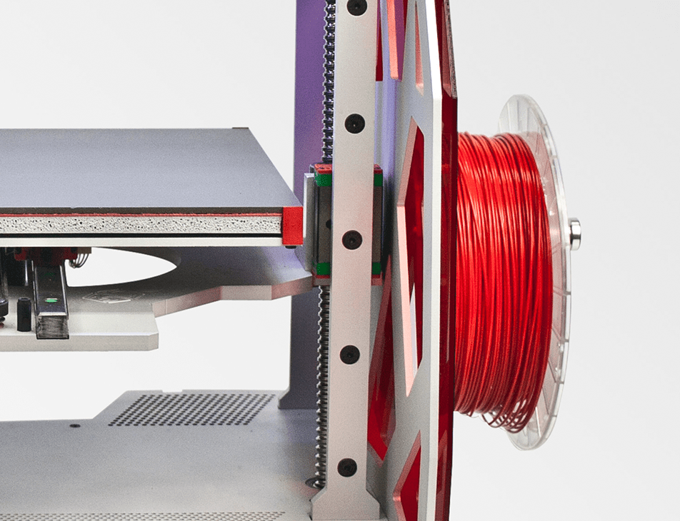 Professional 3D printer 3DGence ONE. Close-up of spool holder with red ABS filament.