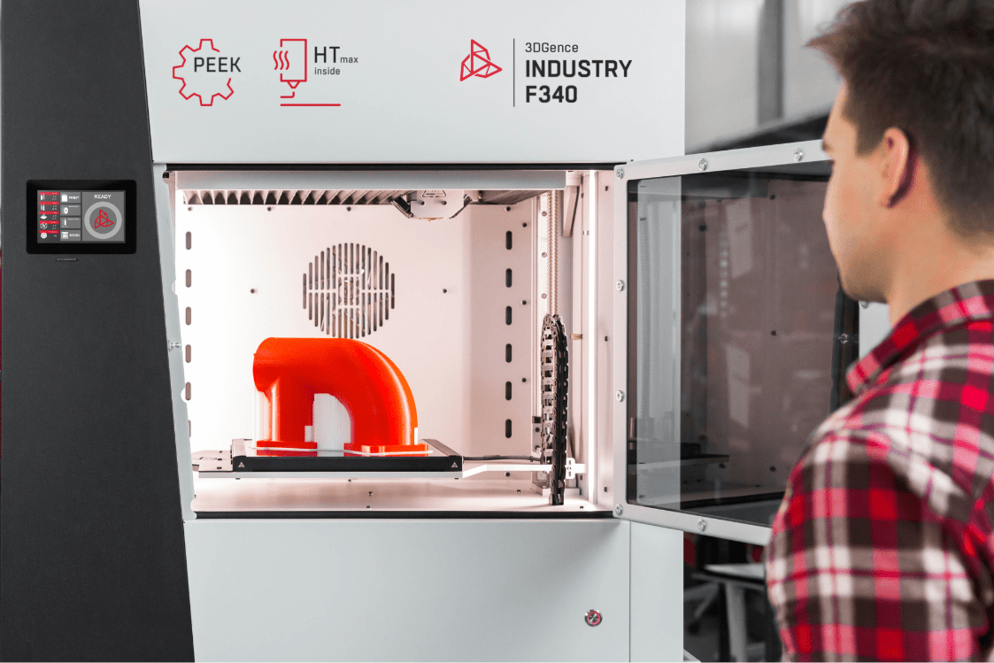 Industrial 3D printer INDUSTRY F340. Man standing in front of the printer. Open printing chamber and red printout inside.