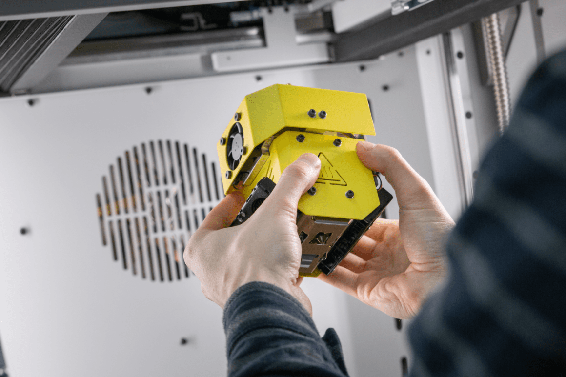 Industrial 3D printer INDUSTRY F340. Close-up of mans hands holding interchangeable printing module HF.