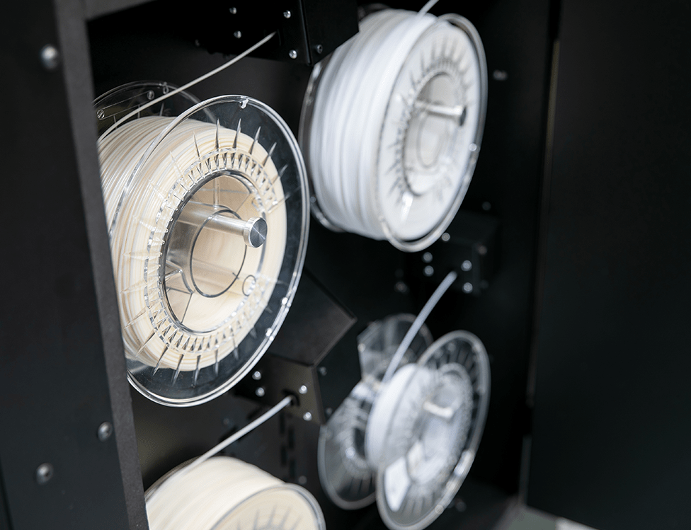 Industrial 3D printer INDUSTRY F340. Close-up of filament chamber with four filaments spools inside. View from an angle.