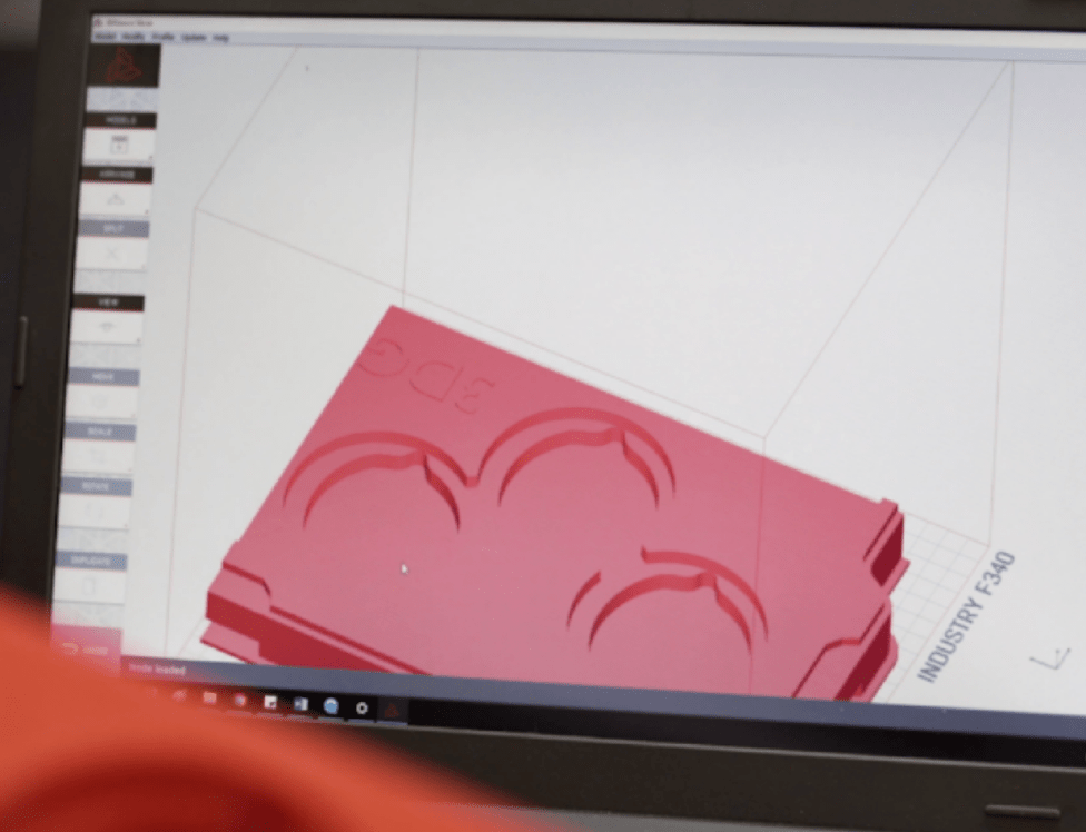 3D model of red transportation tray on laptop screen.