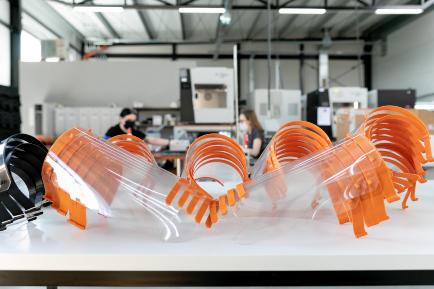 Zbliżenie na kilkanaście przyłbic ochronnych w parku drukarek 3D