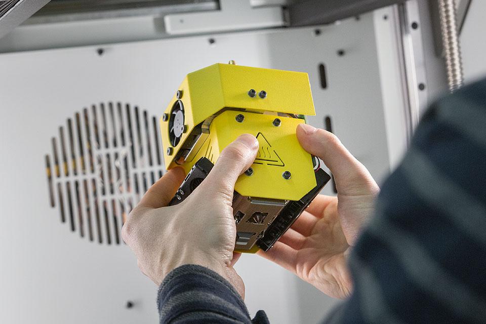 Przemysłowa drukarka 3D INDUSTRY F340. Zbliżenie na mężczyznę trzymającego żółty modłuł HF.