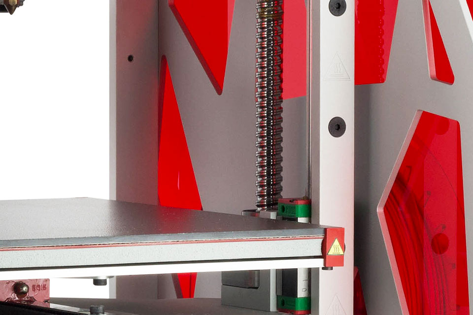Professional 3D printer 3DGence ONE. Close-up of leveling screws and ceramic heatbed.