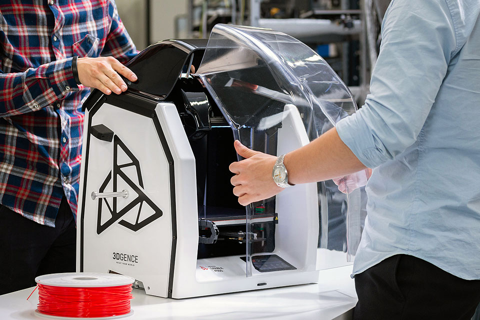 Professional 3D printer 3DGence DOUBLE P255. Close-up on two men's hands taking off enclosure.