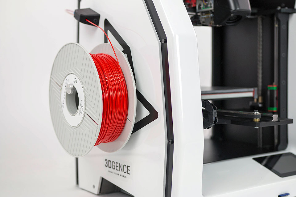 Professional 3D printer 3DGence DOUBLE P255. Close-up of spool holder with red ABS filament.